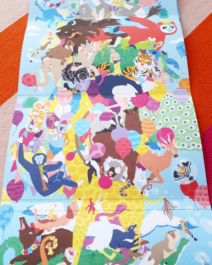 Giraffe blowing balloons in Party Animals fold out picture book by Clea Dieudonne Thames and Hudson